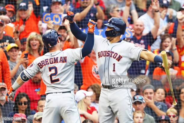 Alex Bregman of the Houston Astros celebrates with Carlos Correa after hitting a solo home run against the Boston Red Sox during the third inning at...