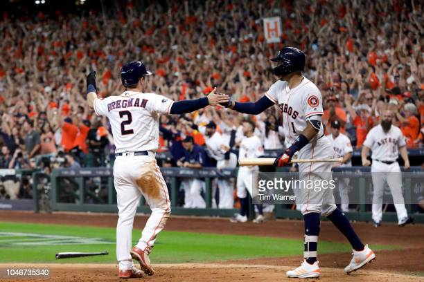 Alex Bregman of the Houston Astros celebrates with Carlos Correa after scoring a run in the sixth inning against the Cleveland Indians during Game...