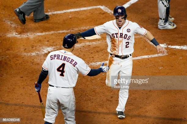 Alex Bregman of the Houston Astros celebrates with his teammate George Springer after scoring off of Brian McCann RBI double against the New York...