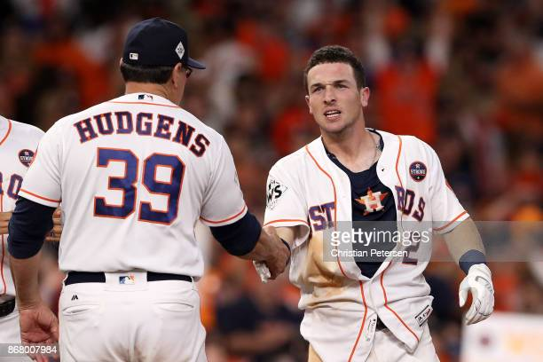 Alex Bregman of the Houston Astros celebrates with hitting coach Dave Hudgens after defeating the Los Angeles Dodgers in the early morning hours...