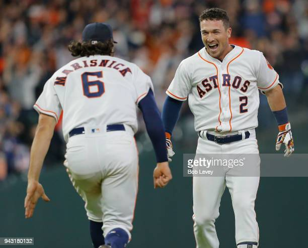Alex Bregman of the Houston Astros celebrates with Jake Marisnick after his walkoff pop fly single in the tenth inning to beat the San Diego Padres...