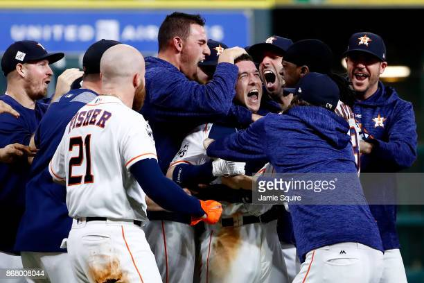 Alex Bregman of the Houston Astros celebrates with teammates after hitting a game-winning single during the tenth inning against the Los Angeles...