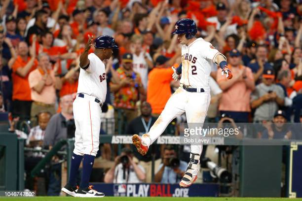 Alex Bregman of the Houston Astros celebrates with third base coach Gary Pettis after he hit a solo home run in the seventh inning against the...
