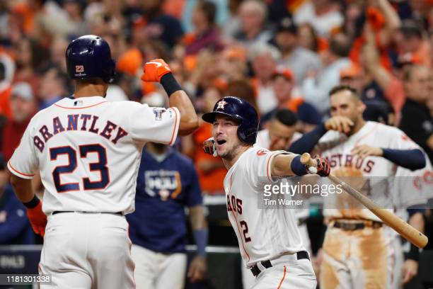 Alex Bregman of the Houston Astros congratulates Michael Brantley after a home run in the eighth inning against the Tampa Bay Rays during game five...
