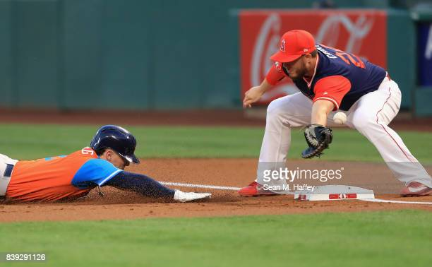 Alex Bregman of the Houston Astros dives back to first base as CJ Cron of the Los Angeles Angels of Anaheim can't handle the throw during the first...