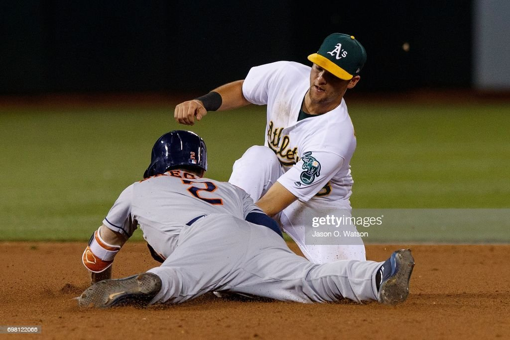 Alex Bregman #2 of the Houston Astros dives into second base for a double ahead of a tag from Chad Pinder #18 of the Oakland Athletics during the ninth inning at the Oakland Coliseum on June 19, 2017 in Oakland, California. The Houston Astros defeated the Oakland Athletics 4-1.