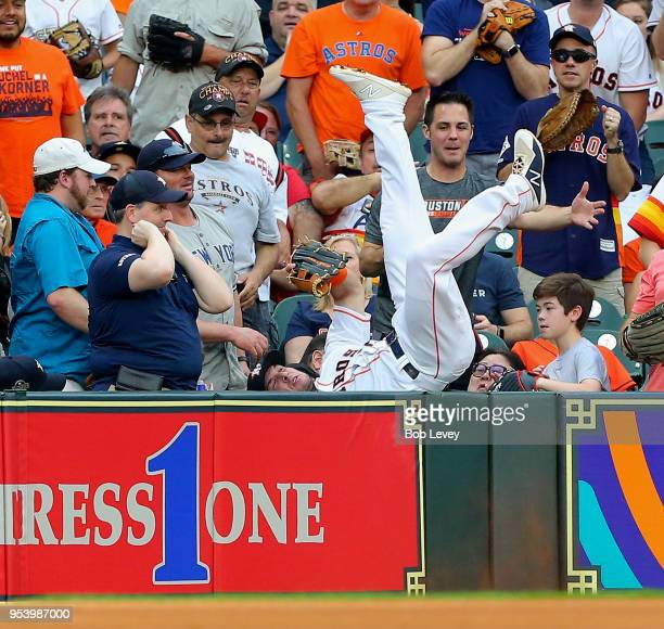 Alex Bregman of the Houston Astros dives into the stands attempting to catch a foul ball off the bat of Didi Gregorius of the New York Yankees at...