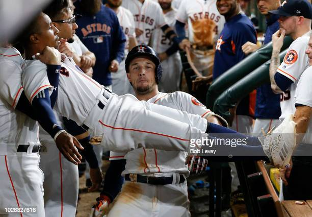 Alex Bregman of the Houston Astros does the limbo with the help of Tony Kemp after hitting a home run in the seventh inning against the Los Angeles...