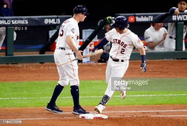 Alex Bregman of the Houston Astros hands his bat to first base coach Don Kelly after hitting a solo home run against the Washington Nationals during...