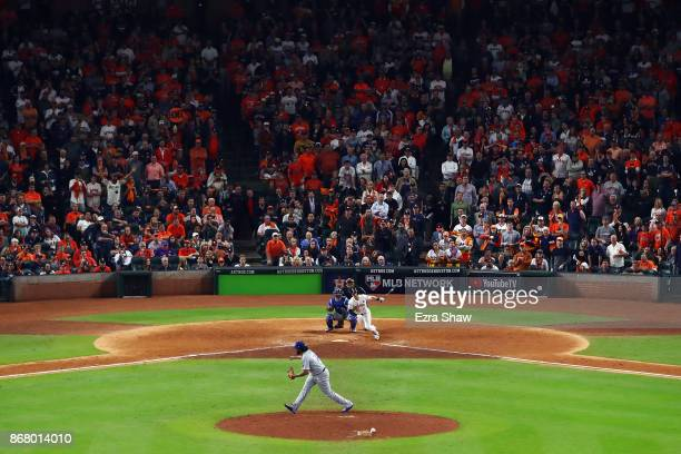 Alex Bregman of the Houston Astros hits a game-winning single during the tenth inning against Kenley Jansen of the Los Angeles Dodgers in game five...