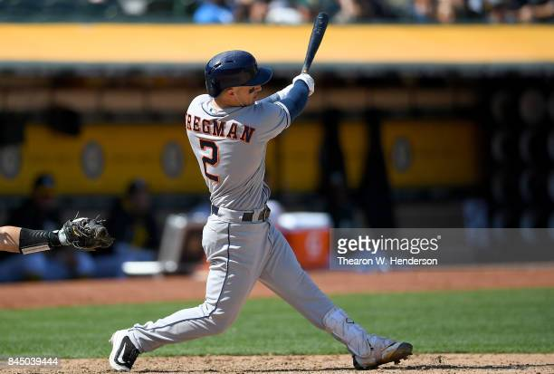 Alex Bregman of the Houston Astros hits an RBI double scoring Max Stassi against the Oakland Athletics in the top of the fifth inning during game one...