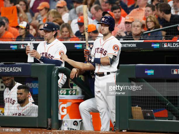 Alex Bregman of the Houston Astros holds a bat in the dugout in the sixth inning against the Tampa Bay Rays during game five of the American League...