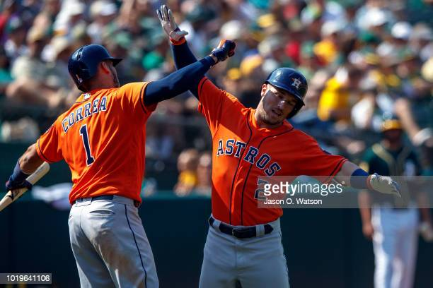 Alex Bregman of the Houston Astros is congratulated by Carlos Correa after hittng a home run against the Oakland Athletics during the seventh inning...