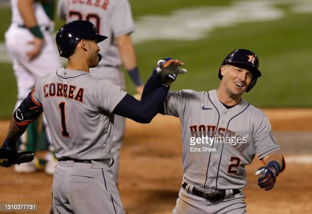 Alex Bregman of the Houston Astros is congratulated by Carlos Correa after he hit a home run in the eighth inning against the Oakland Athletics...