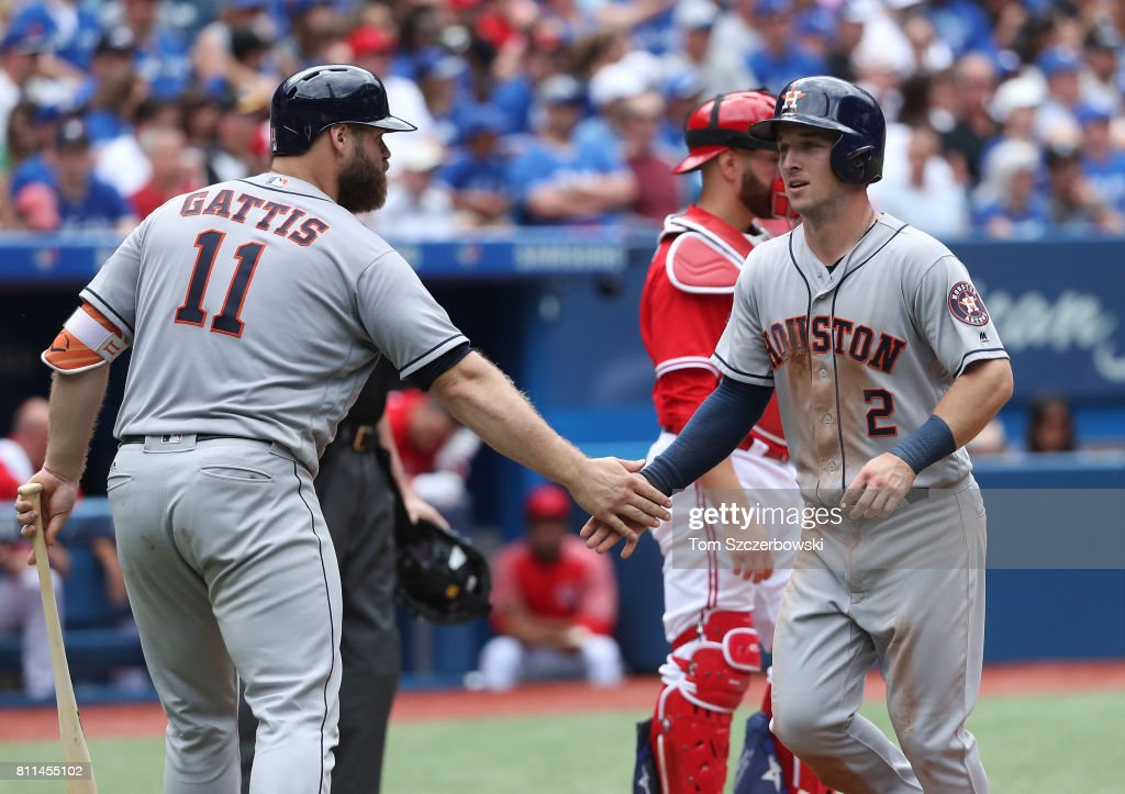 Alex Bregman #2 of the Houston Astros is congratulated by Evan Gattis #11 after scoring a run in the fourth inning during MLB game action against the Toronto Blue Jays at Rogers Centre on July 9, 2017 in Toronto, Canada.