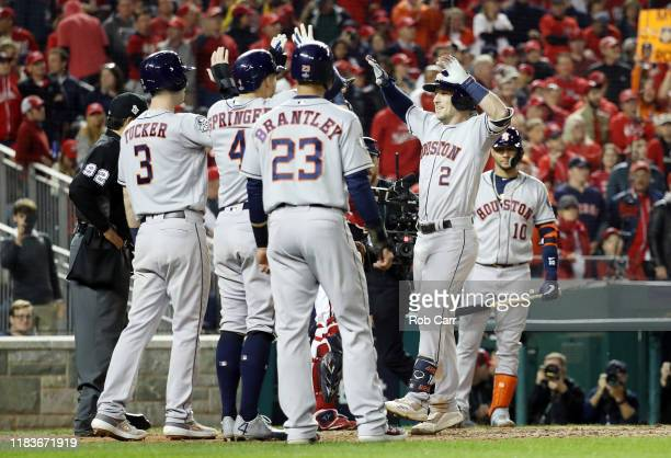Alex Bregman of the Houston Astros is congratulated by his teammates after hitting a grand slam home run against the Washington Nationals during the...