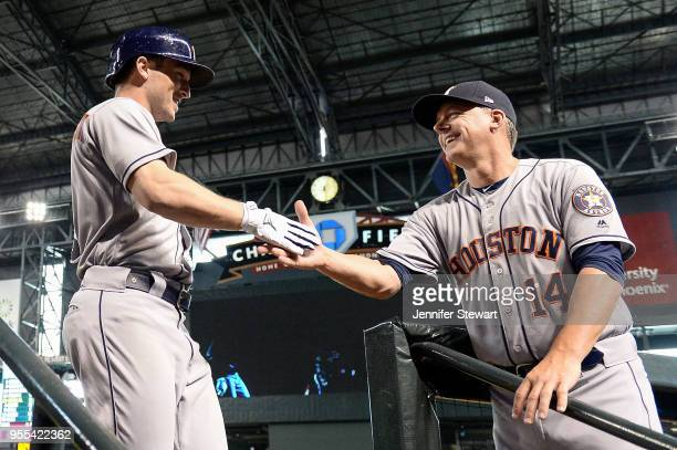 Alex Bregman of the Houston Astros is congratulated by manager AJ Hinch after hitting a solo home run in the second inning of the MLB game against...