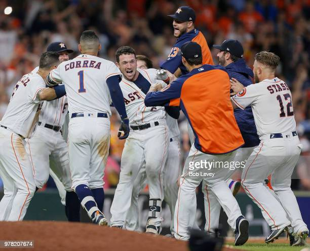 Alex Bregman of the Houston Astros is mobbed by his teammates after hitting a walkoff double in the ninth inning against the Tampa Bay Rays for a 5-4...