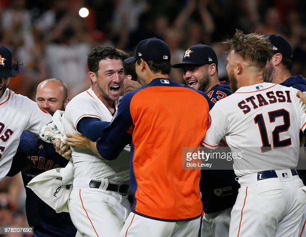 Alex Bregman of the Houston Astros is mobbed by his teammates after hitting a walkoff double in the ninth inning against the Tampa Bay Rays for a 54...