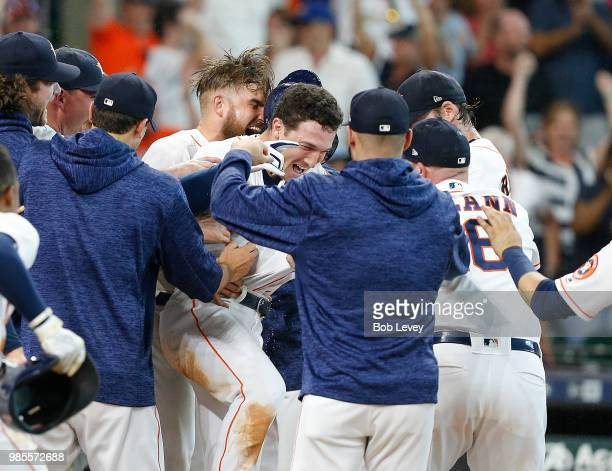 Alex Bregman of the Houston Astros is surrounded by teammates after hitting a walkoff tworun home run in the ninth inning to give the Houston Astros...