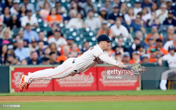 Alex Bregman of the Houston Astros makes a diving catch on a line drive by Gio Urshela of the New York Yankees in the fourth inning at Minute Maid...