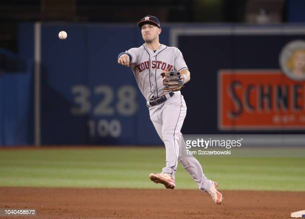 Alex Bregman of the Houston Astros makes the play and throws out the baserunner in the eighth inning during MLB game action against the Toronto Blue...