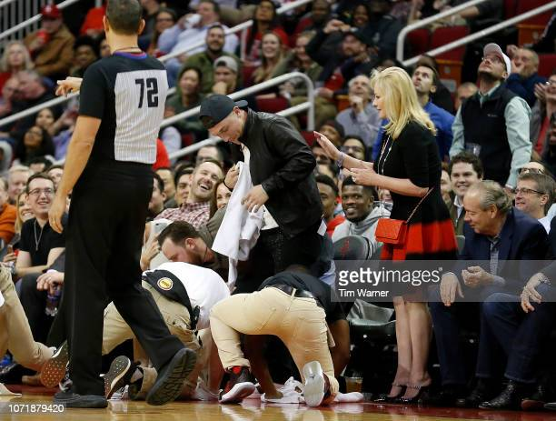 Alex Bregman of the Houston Astros reacts after PJ Tucker of the Houston Rockets crashed into him while diving for a loose ball in the first half...