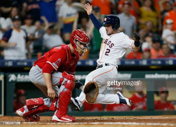 Alex Bregman of the Houston Astros slices behind catcher Dustin Garneau of the Los Angeles Angels of Anaheim to score on a double by Yordan Alvarez...