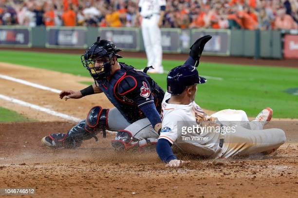 Alex Bregman of the Houston Astros slides safely past the tag from Yan Gomes of the Cleveland Indians to score a run in the sixth inning of Game Two...