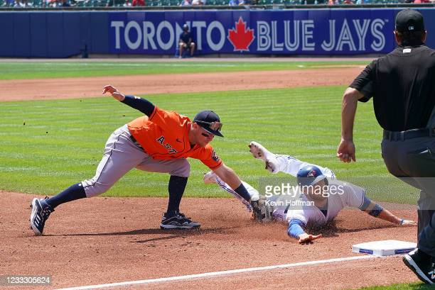 Alex Bregman of the Houston Astros tags out Danny Jansen of the Toronto Blue Jays at third base during the third inning at Sahlen Field on June 6,...