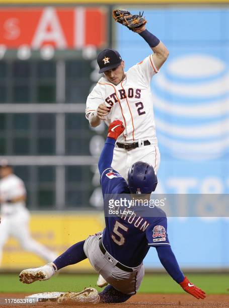 Alex Bregman of the Houston Astros tags out Willie Calhoun of the Texas Rangers attempting to steal second base at Minute Maid Park on September 18...