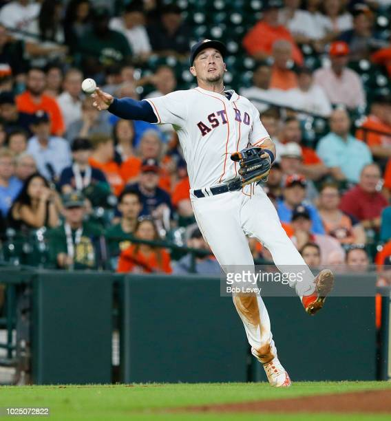 Alex Bregman of the Houston Astros throws to first base but unable to retire Chad Pinder of the Oakland Athletics on a soft ground ball in the second...