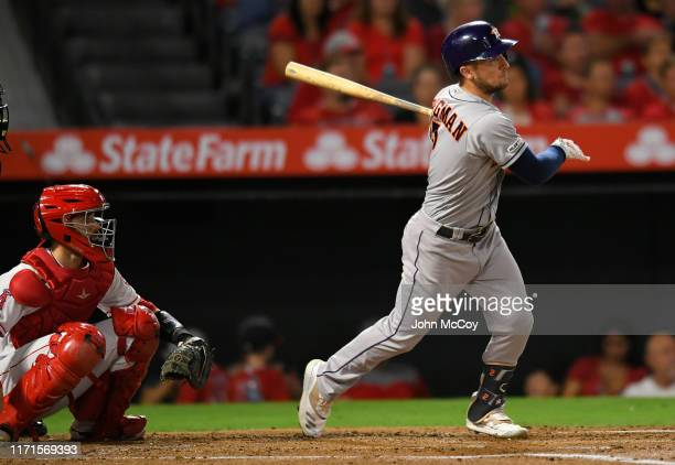 Alex Bregman of the Houston Astros watches his home run ball while Anthony Bemboom of the Los Angeles Angels looks on in the first inning at Angel...