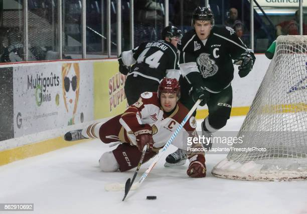 Alex Breton of the Gatineau Olympiques battles for a loose puck against Elijah Francis of the Acadie-Bathurst Titan on October 18, 2017 at Robert...