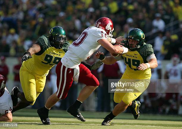 Alex Brink of the Washington State Cougars is pressured by Nick Reed and Jeremy Gibbs of the Oregon Ducks at Autzen Stadium October 13 2007 in Eugene...
