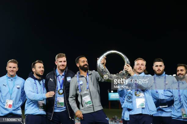 Alex Brosque and Rhyan Grant of Sydney FC pose with the ALeague trophy with team mates during the AFC Asian Champions League match between Sydney FC...