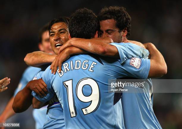 Alex Brosque of Sydney celebrates with Nick Carle and Mark Bridge of Sydney after scoring the opening goal during the round one A-League match...