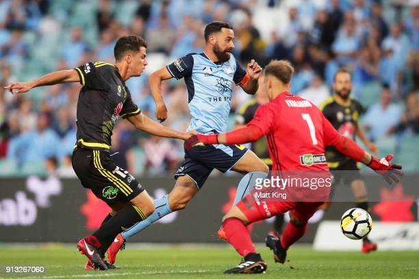 Alex Brosque of Sydney FC beats defender Marco Rossi of Wellington Phoenix and Wellington Phoenix goalkeeper Lewis Italiano to score the first goal...