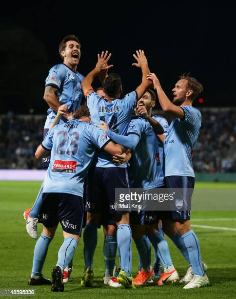Alex Brosque of Sydney FC celebrates with team mates after scoring a goal as Joshua Brillante jumps over the top during the A-League Semi Final match...