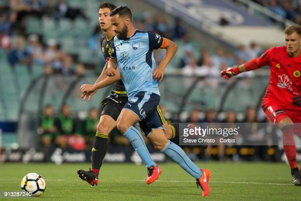 Alex Brosque of Sydney FC gets past Wellington's Lewis Italiano and Scott Galloway to score during the round 19 ALeague match between Sydney FC and...