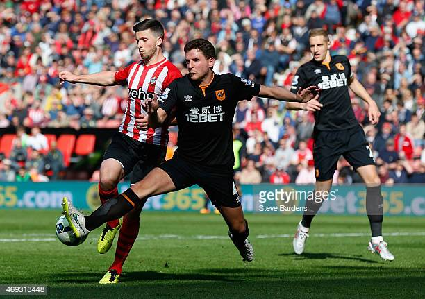 Alex Bruce of Hull City challenges Shane Long of Southampton to concede a penalty during the Barclays Premier League match between Southampton and...