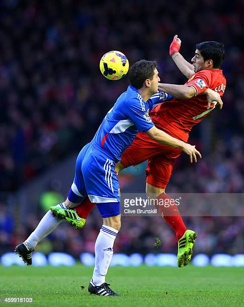 Alex Bruce of Hull City clashes with Luis Suarez of Liverpool during the Barclays Premier League match between Liverpool and Hull City at Anfield on...