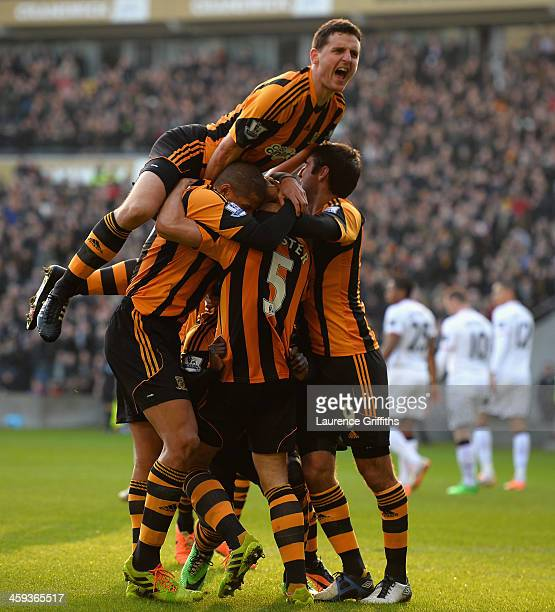 Alex Bruce of Hull City jumps for joy as the team mobb James Chester after scoring the opening goal during the Barclays Premier League match between...