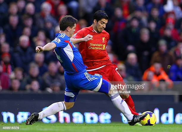 Alex Bruce of Hull City tackles Luis Suarez of Liverpool during the Barclays Premier League match between Liverpool and Hull City at Anfield on...