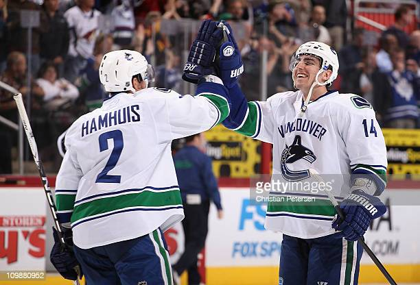 Alex Burrows and Dan Hamhuis of the Vancouver Canucks celebrate after Hamhuis scored the game winning goal against the Phoenix Coyotes in overtime of...
