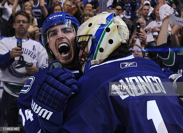 Alex Burrows and goaltender Roberto Luongo of the Vancouver Canucks celebrate after defeating the San Jose Sharks 3-2 in double-overtime in Game Five...