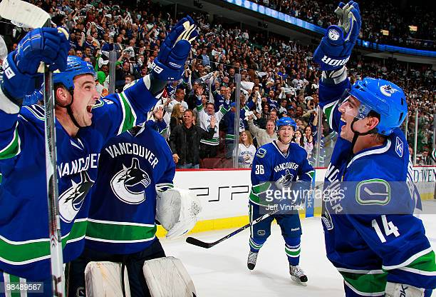 Alex Burrows and Shane O'Brien of the Vancouver Canucks celebrate the gamewinning goal during overtime in Game One of the Western Conference...