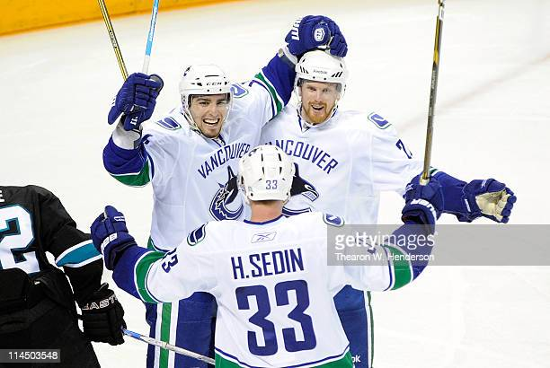 Alex Burrows, Henrik Sedin and Daniel Sedin of the Vancouver Canucks celebrate Burrows' goal in the third period against the San Jose Sharks in Game...