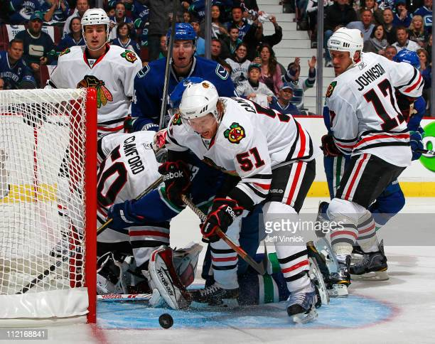 Alex Burrows of the Vancouver Canucks and Brian Campbell of the Chicago Blackhawks watch the rebound in the Chicago crease in Game One of the Western...