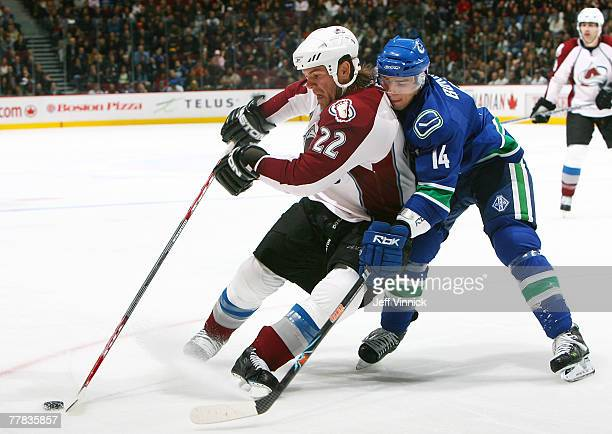 Alex Burrows of the Vancouver Canucks and Scott Hannan of the Colorado Avalanche battle for the puck during their game at General Motors Place on...